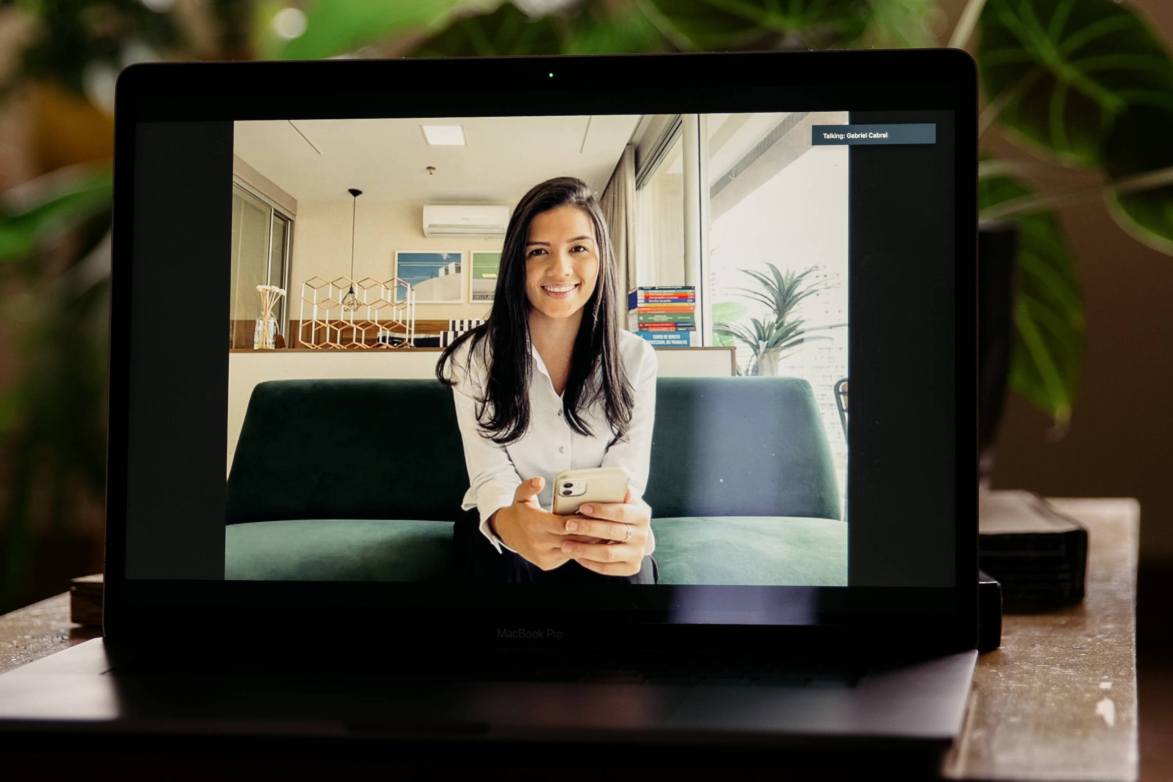 Tela de computador onde se vê mulher branca sorrindo e com braço esticado para segurar o celular com que se filma. Ao fundo ambiente de escritório