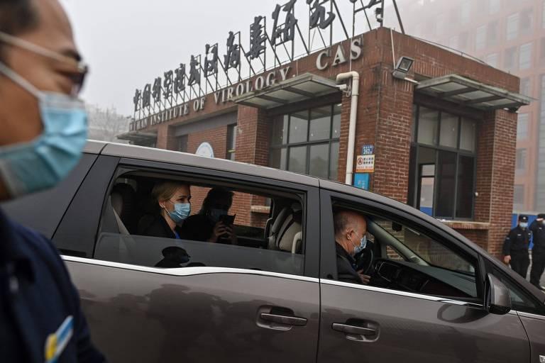 Em carro escuro, profissionais de máscara em frente a fachada de tijolos