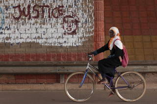 FILE PHOTO: A girl rides a bicycle past graffiti reading