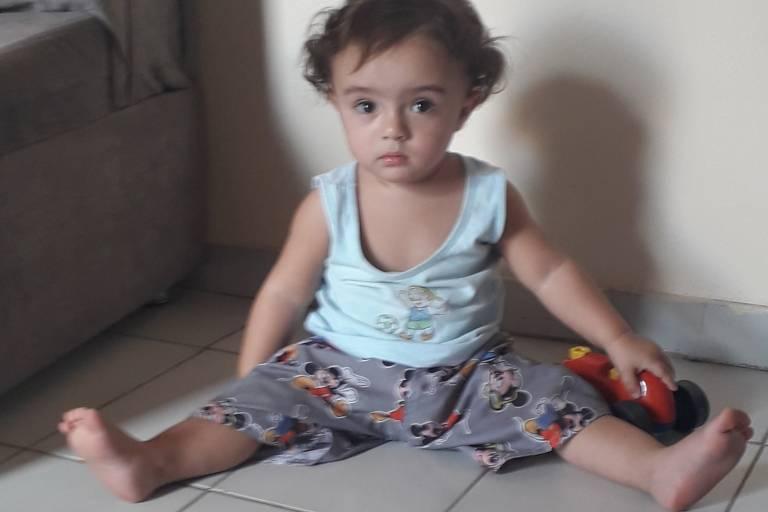 um bebê sentado com as perninhas abertas em um chão branco de azulejo
