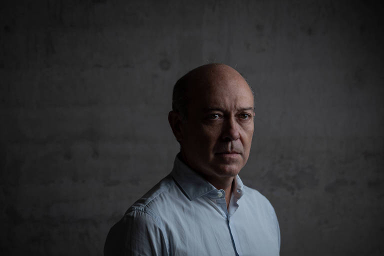 Homem de camisa azul clara com parede cinza ao fundo