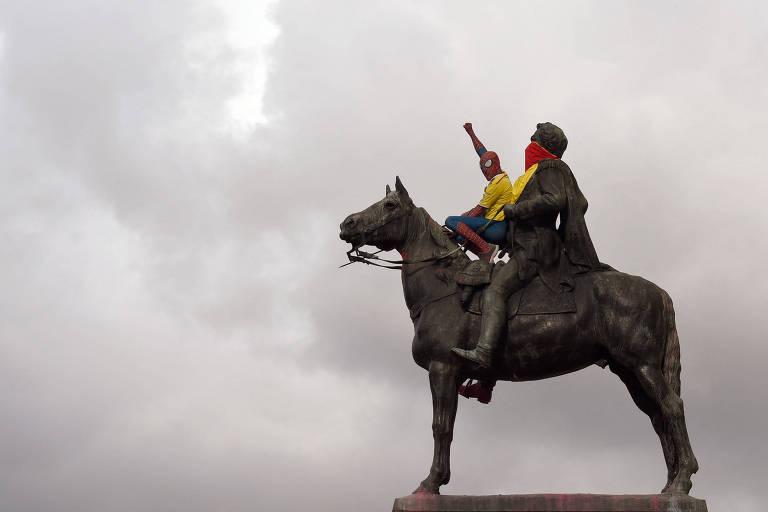 Um homem vestido de Homem-Aranha ergue o punho cerrado em cima da estátua deSimon Bolívar durante protestos contra o governo em Bogotá