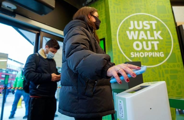 Cliente escaneia um código pelo celular na entrada da loja Amazon Fresh