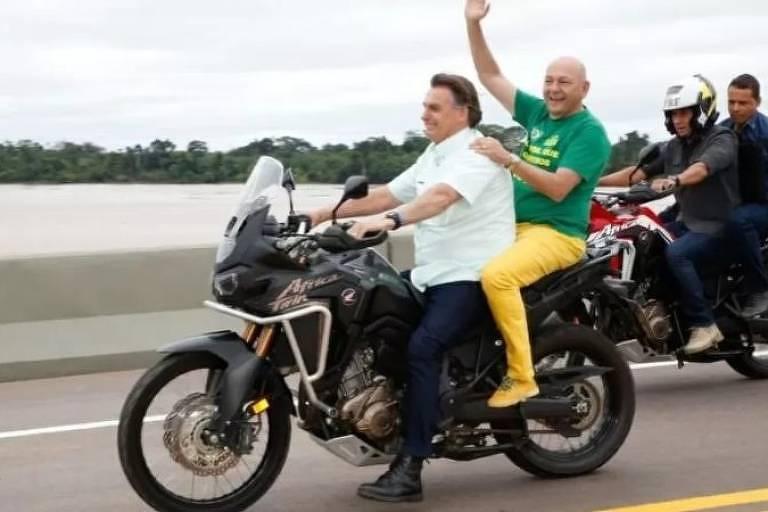 O presidente Jair Bolsonaro e Luciano Hang circulam de moto, sem capacete, após a cerimonia de inauguração da Ponte do Abunã, sobre o Rio Madeira