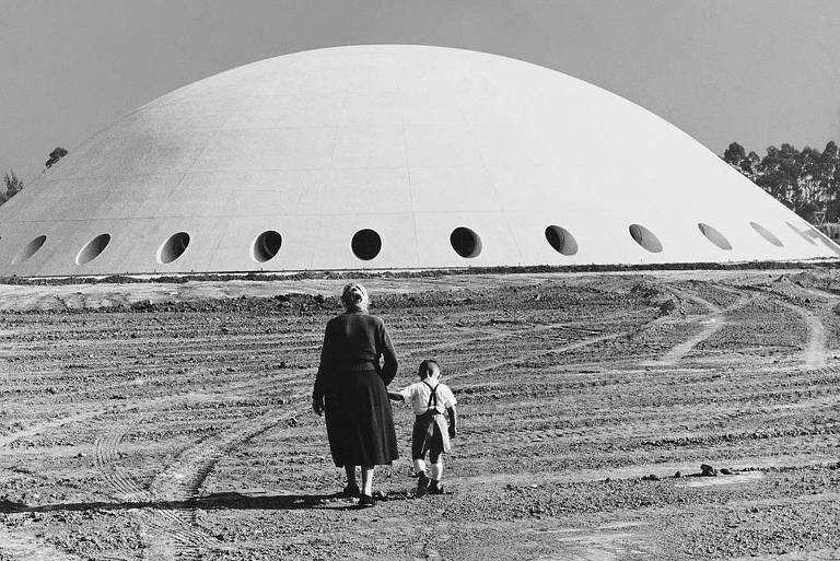 Fotografia de German Lorca mostra uma mulher idosa e uma criança de mãos dadas em frente à Oca, no parque Ibirapuera, em 1954