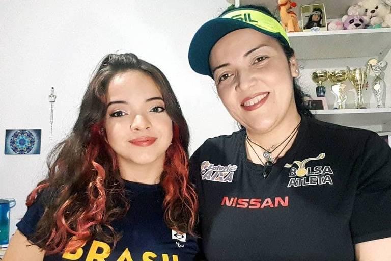 Mulher jovem com camiseta do Brasil ao lado da mãe, que usa viseira com as cores do país