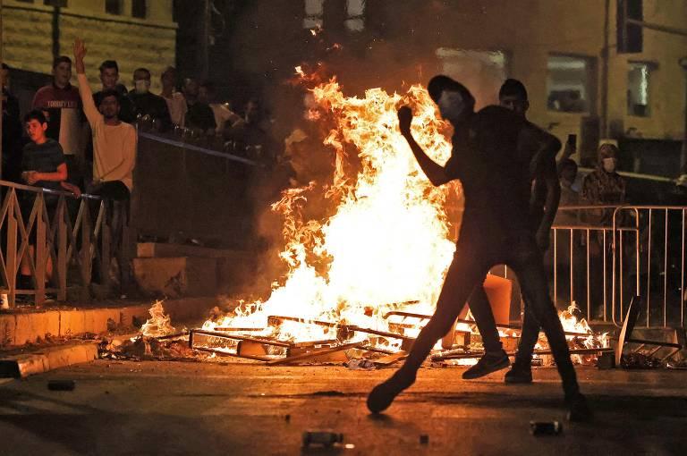 Um manifestante palestino atira pedras contra as forças de segurança israelenses na Cidade Velha de Jerusalém