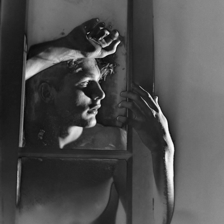 """Na fotografia """"Le Diable au Corps"""" (1949), de German Lorca, um belo rapaz encosta o corpo numa vidraça, o olhar perdido no horizonte e uma das mãos do lado de cá, de quem vê a cena fora do quadro; as folhas de vidro da janela esquartejam a cena, um campo geométrico, de ângulos retos, que dão ordem à carne"""