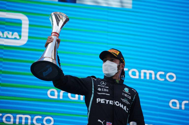 Homem de roupa de corrida de fórmula 1, boné e máscara segurando troféu