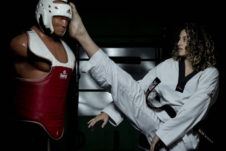 Mulher de uniforme de luta tipo kimono branco chutando boneco de treino na cabeça