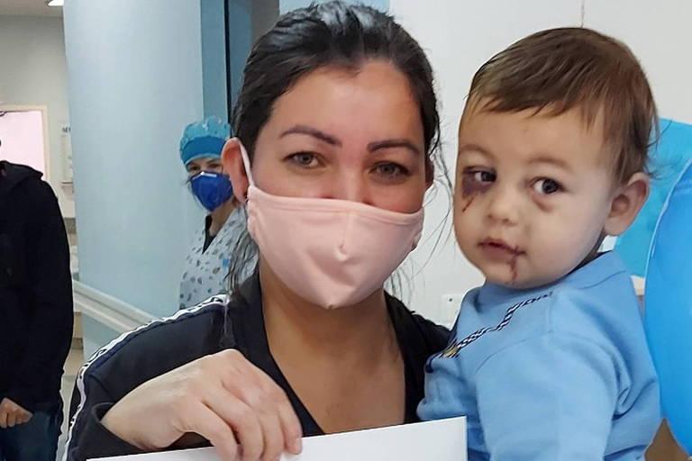 Imagem mostra mulher usando máscaras e segurando, com o braço esquerdo, o bebê que sobreviveu ao ataque