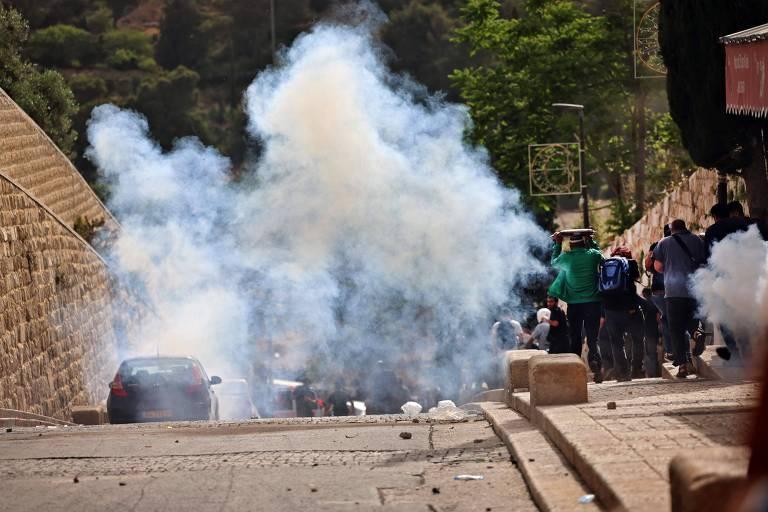 Nuvem de gás lacrimogêneo ofusca visão de grupo de pessoas