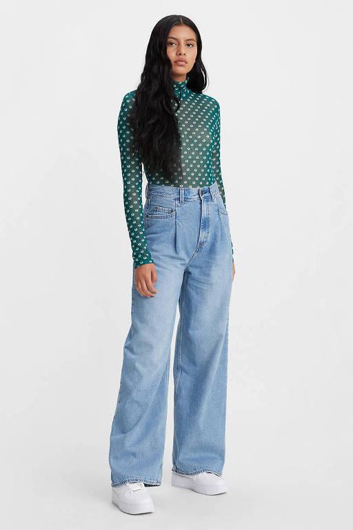 Mulher negra modela com blusa verde e calça jeans azul clara de cintura alta