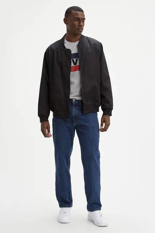 Homem negro modela com moletom verde escuro, jeans azul e tênis branco