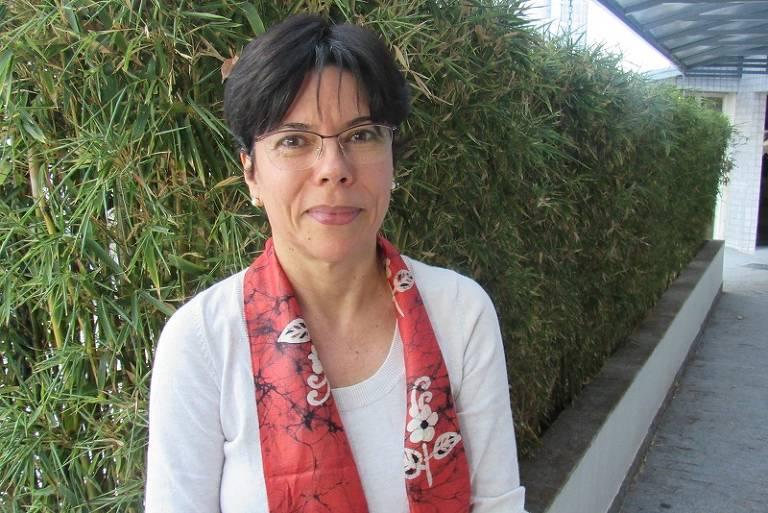 Mulher branca de cabelos curtos e castanho escuros, usa uma blusa branca de manga longa com um lenço laranja no pescoço