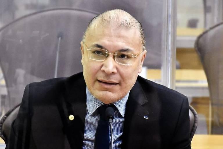 Um homem calvo, de óculos e terno