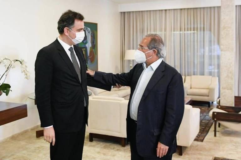 O presidente do Senado, Rodrigo Pacheco e o ministro Paulo Guedes, ambos de pé, se cumprimentam