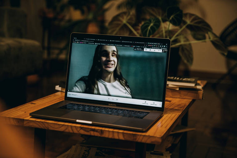 Sobre uma mesinha, computador mostra a imagem de Lucas Radaelli durante chamada de vídeo