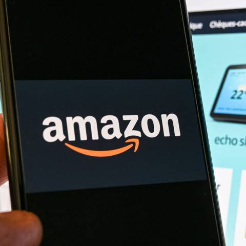 (FILES) In this file photograph taken on November 18, 2020 in Lille, a person poses with a smartphone showing an Amazon logo, in front of a computer screen displaying the home page of Amazon France sales website. - Amazon said on May 10, 2021 it blocked more than 10 billion suspected listings of counterfeit goods on its platform last year as part of a global crackdown in the face of pressure from consumers, brands and regulators. The e-commerce colossus made the announcement in its first