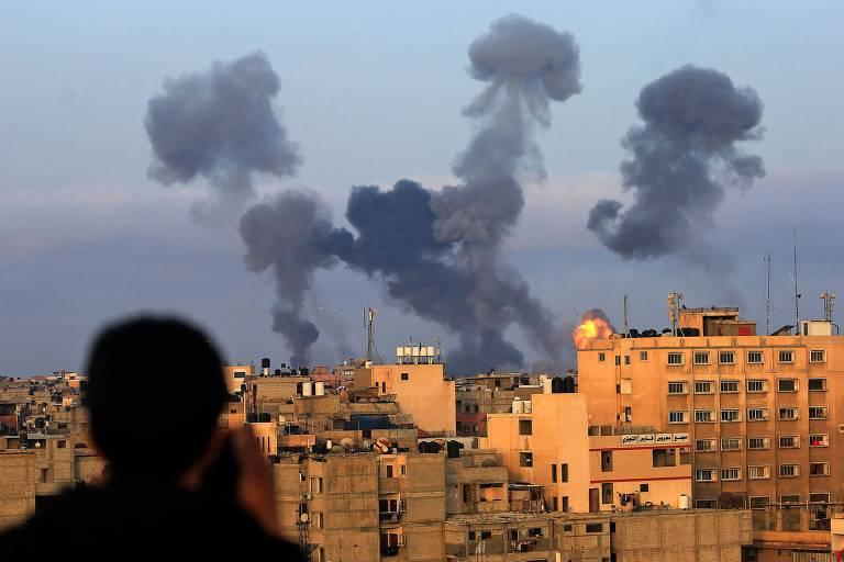 Menino observa pilares de fumaça subirem de prédios que foram atingidos por mísseis