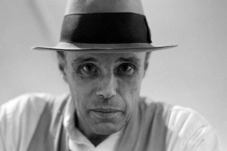 Retrato de Joseph Beuys em preto e branco; ele usa chapéu e olha para a câmera