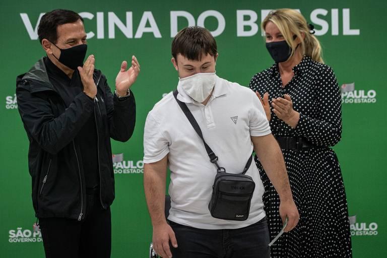João Doria, à esquerda, aplaude jovem Victor com Síndrome de Down, ao centro, acompanhado por Bia Doria, que também aplaude, à direita