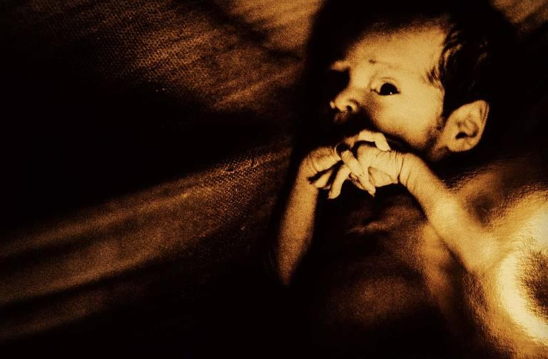 Retrato de bebê ianomâmi em rede; ele olha para a câmera e tem os dedos das mãos cruzados