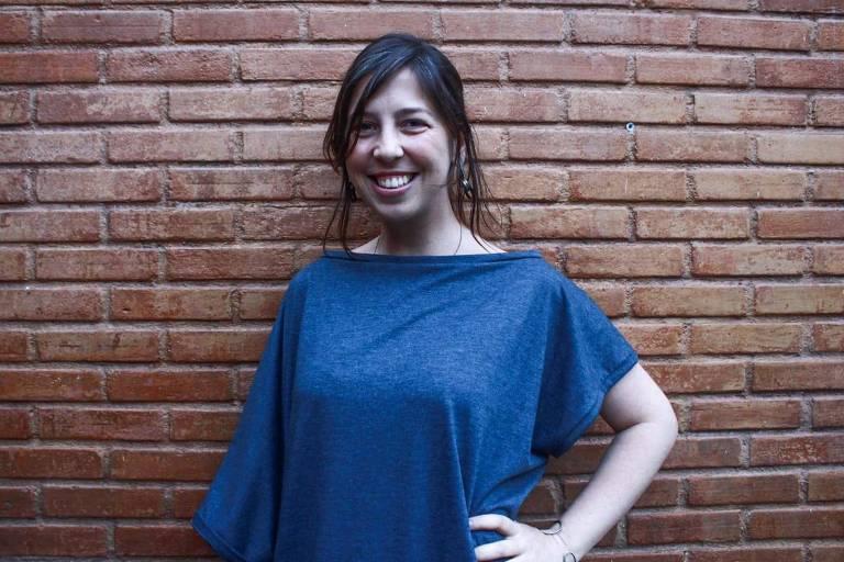 mulher de blusa azul sorri para a foto. atrás há uma parede de tijolos.