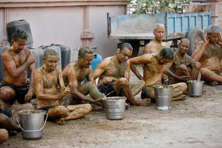 Em Ahmedabad, na Índia, pessoas passam esterco de vaca em seus corpos na crença de que a prática pode aumentar a imunidade contra Covid
