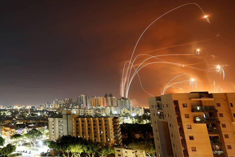 Em céu escuro, faixas de fumaça indicam trajetória de mísseis