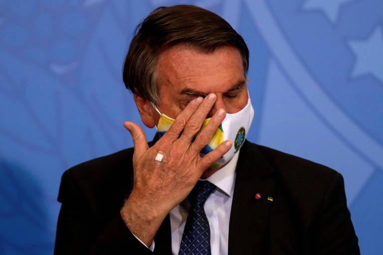 Homem branco usa terno preto, máscara facial com as cores do brasil e coça o olho enquanto está sentado em frente à microfone