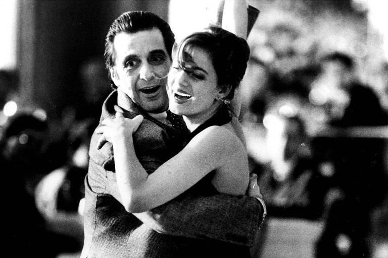 Homem e mulher brancos dançam agarrados um ao outro e dão risada