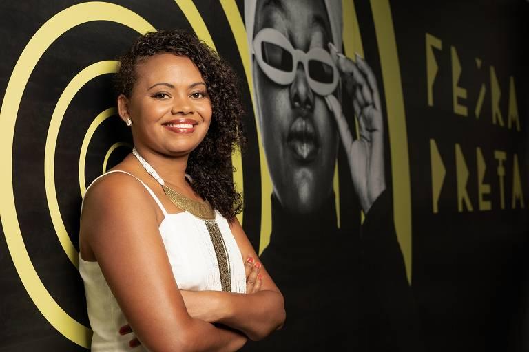 mulher negra cruza os braços e sorri, de roupa branca, em frente a um painel preto com espirais coloridas