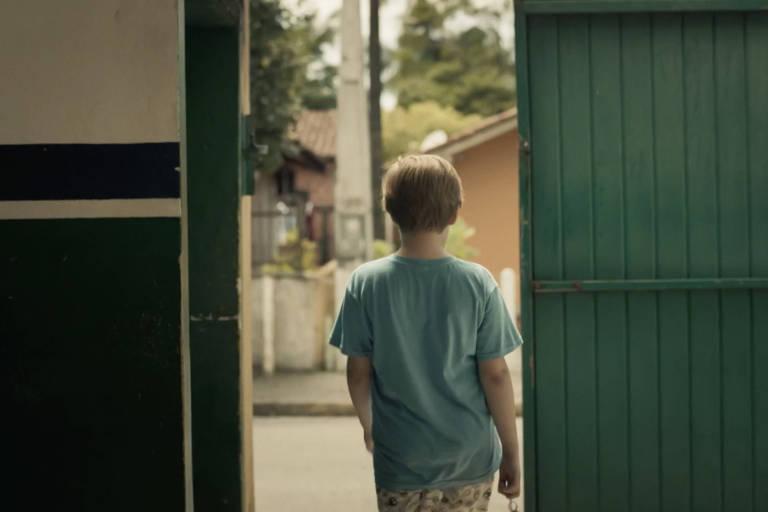 menino branco e loiro é visto a partir de porta verde semi-aberta