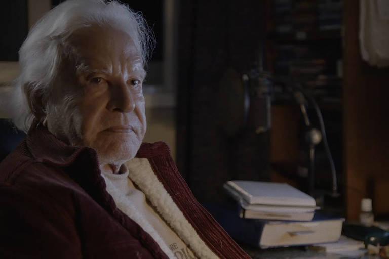 homem de cabelos brancos sentado diante de mesa com livros