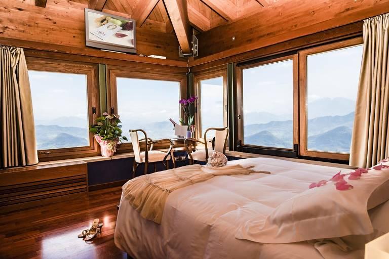 Quarto com teto de madeira e uma cama de casal coberta de colcha cor de rosa deixa ver, por duas paredes totalmente envidraçadas,  um enorme vale