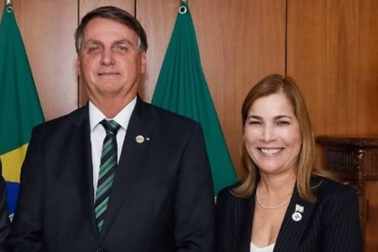 O presidente, de terno escuro, gravata listrada e camisa branca, está ao lado da médica, que tem os cabelos castanhos com as pontas mais clars e sorri, usando um blazer e uma camiseta branca; ao fundo, se entrevee a bandeira do Brasil