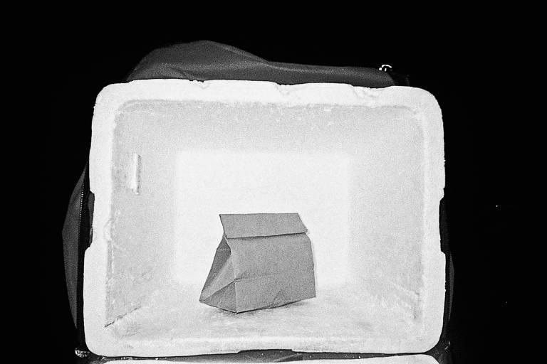 bolsa-isopor de entregador de comida aberta e dentro há um pacote de sacola de papelão