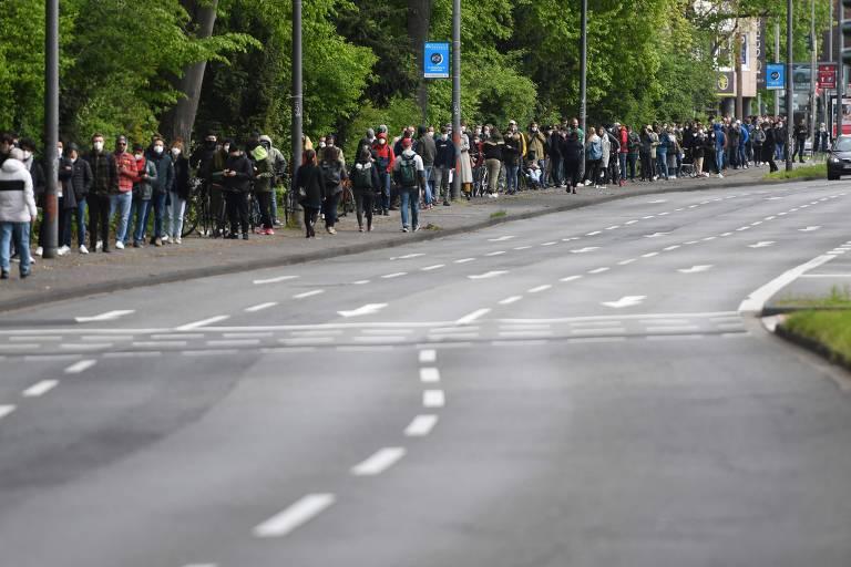 Centenas de pessoas aguardam em fila numa calçada