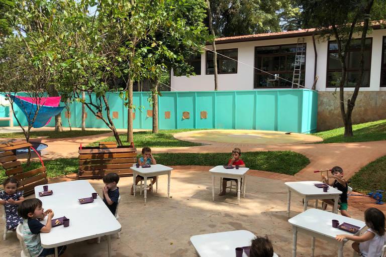 Foto mostra um pátio com algumas árvores e mesas espaçadas; ao fundo um muro azulado e uma construção baixa