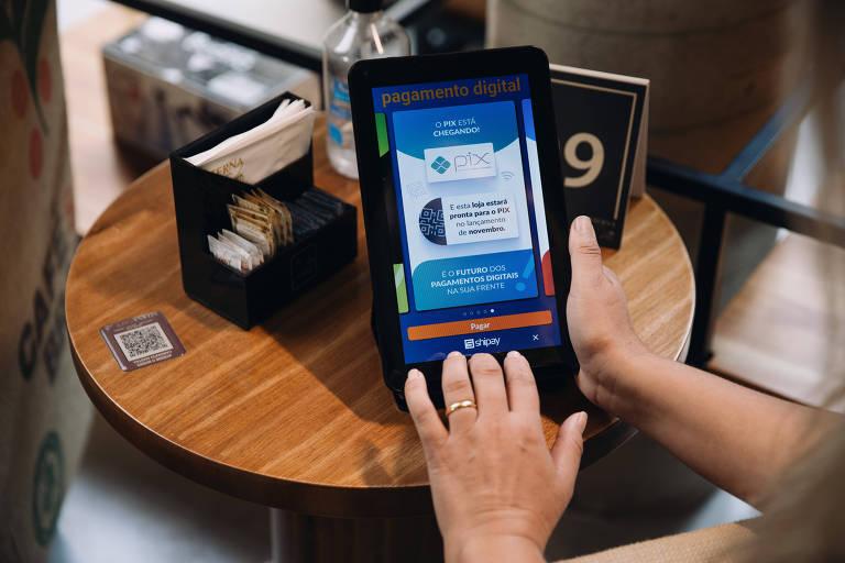 Mãos mexem em tablet sobre uma mesa