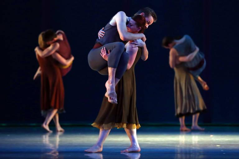 Homem segura mulher em cima de palco ao lado de vários dançarinos