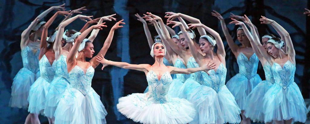 Várias mulheres com vestes de balé dançam em cima de palco