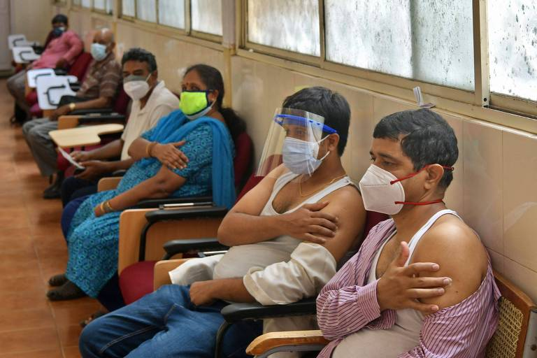 Vemos seis pessoas, homens e mulheres, sentados em bancos juntos a uma parede com uma janela, a maioria deles segurando o braço esquerdo, após terem tomado vacina