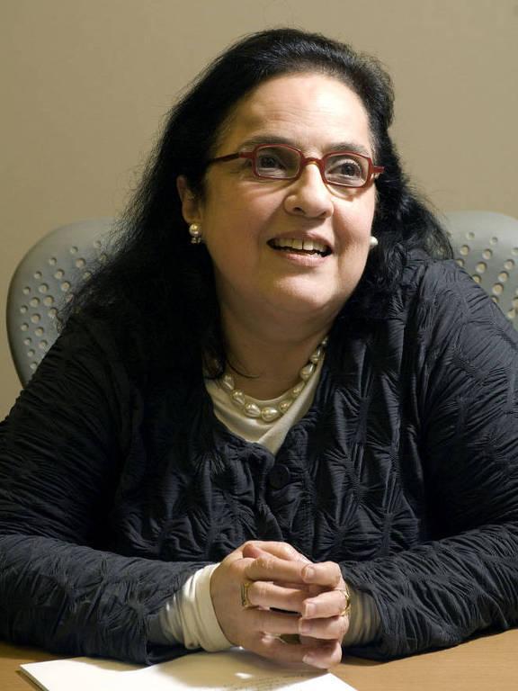 Rosa Freire D'Aguiar sentada com mão cruzada sobre uma mesa