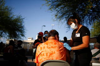A healthcare worker from the El Paso Fire Department administers the Moderna vaccine against the coronavirus disease (COVID-19), in El Paso