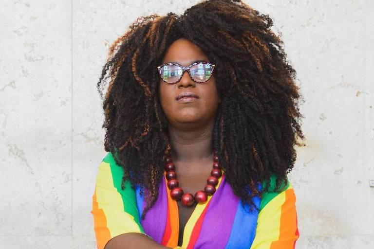 A vereadora Benny Briolly posa para foto com roupas coloridas e óculos escuros