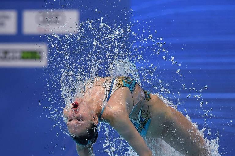 Atleta se ergue de piscina, fazendo com que gotículas de água se despendam de seu corpo