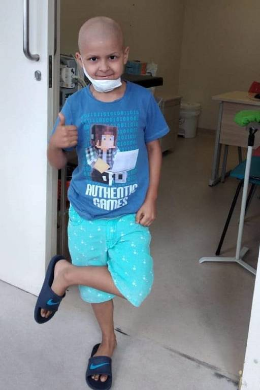 menino faz joia de pé. veste roupa azul e atrás há quarto de hospital