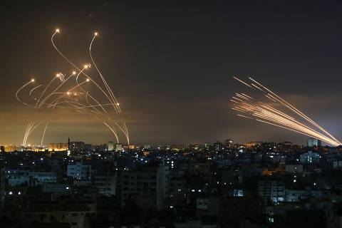 TOPSHOT - Rockets are seen in the night sky fired towards Israel from Beit Lahia in the northern Gaza Strip on May 14, 2021. - Israel bombarded Gaza with artillery and air strikes on Friday, May 14, in response to a new barrage of rocket fire from the Hamas-run enclave, but stopped short of a ground offensive in the conflict that has now claimed more than 100 Palestinian lives.
